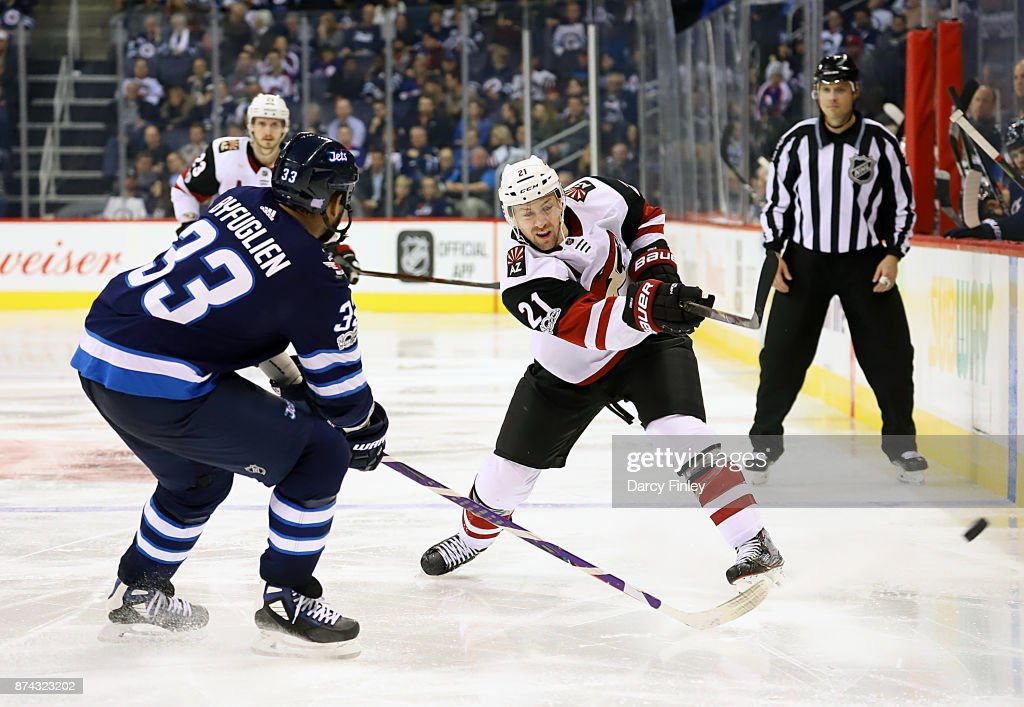 Derek Stepan #21 of the Arizona Coyotes shoots the puck down the ice past a defending Dustin Byfuglien #33 of the Winnipeg Jets during third period action at the Bell MTS Place on November 14, 2017 in Winnipeg, Manitoba, Canada.