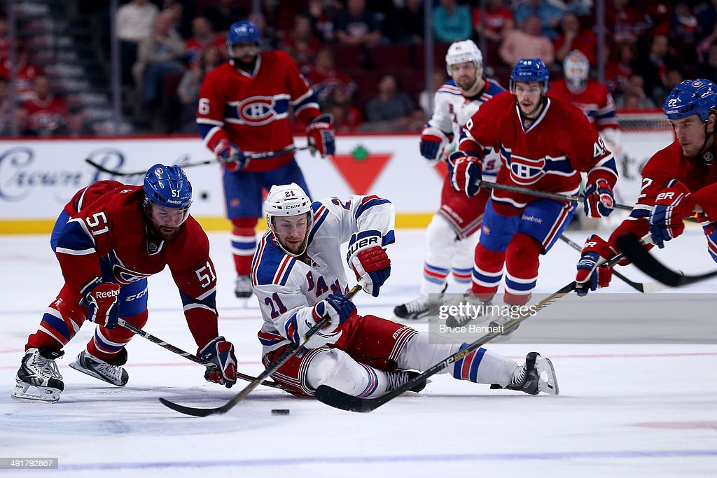 Derek Stepan #21 of the New York Rangers and David Desharnais #51 of the Montreal Canadiens battle for the puck in the third period in Game One of the Eastern Conference Finals of the 2014 NHL Stanley Cup Playoffs at the Bell Centre on May 17, 2014 in Montreal, Canada.