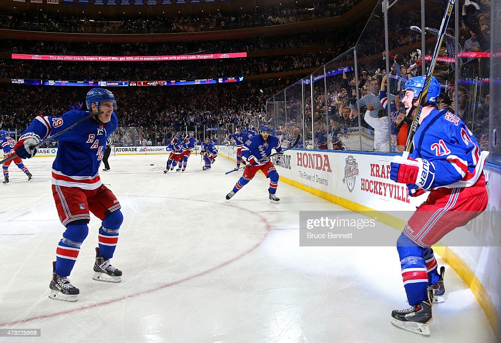Derek Stepan of the New York Rangers celebrates Jesper Fast and his team after scoring the game winning goal in overtime against the Washington...