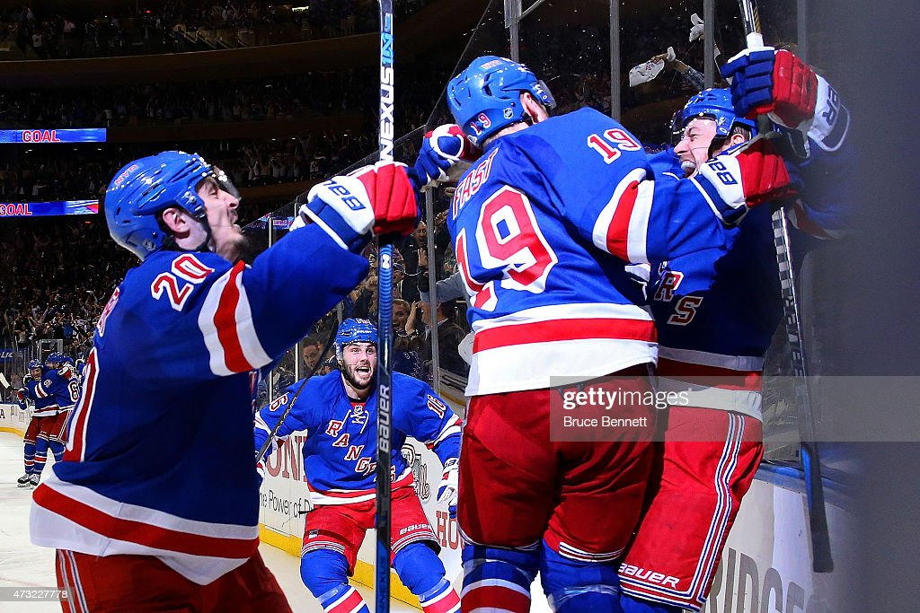 Derek Stepan of the New York Rangers celebrates with Chris Kreider Jesper Fast and his team after scoring the game winning goal in overtime against...
