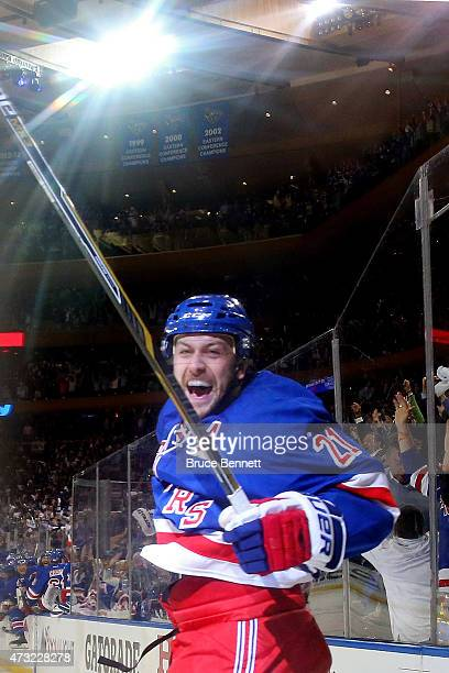 Derek Stepan of the New York Rangers celebrates with his team after scoring the game winning goal in overtime against the Washington Capitals to win...