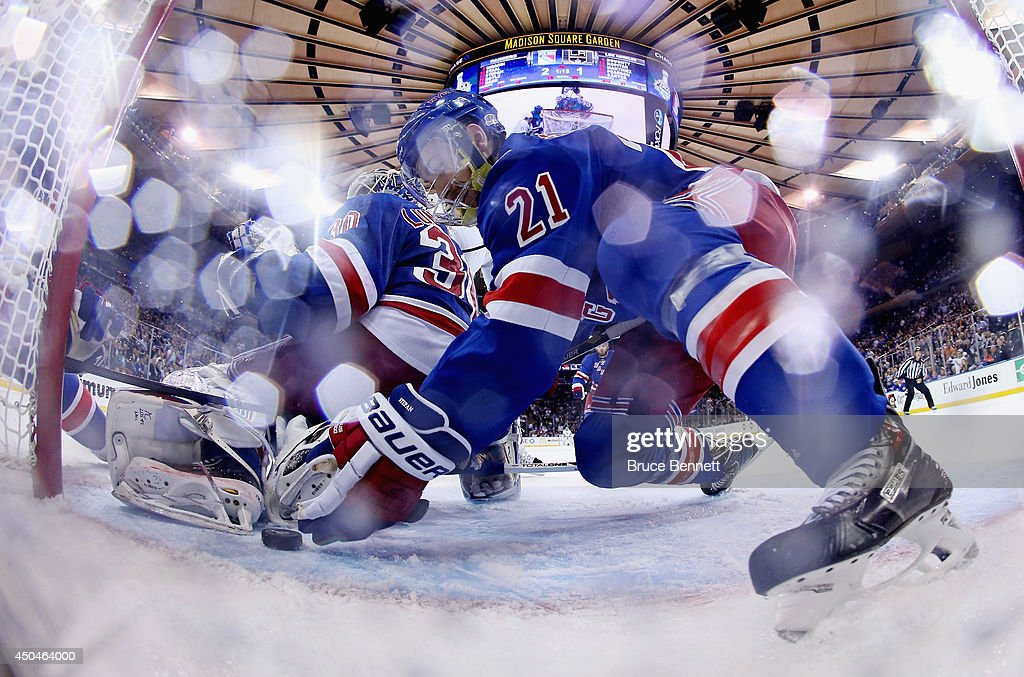Derek Stepan of the New York Rangers clears the puck from the goal line behind Henrik Lundqvist of the New York Rangers during the third period of...