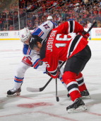 Derek Stepan of the New York Rangers faces off against Jacob Josefson of the New Jersey Devils during the game at the Prudential Center on October 19...