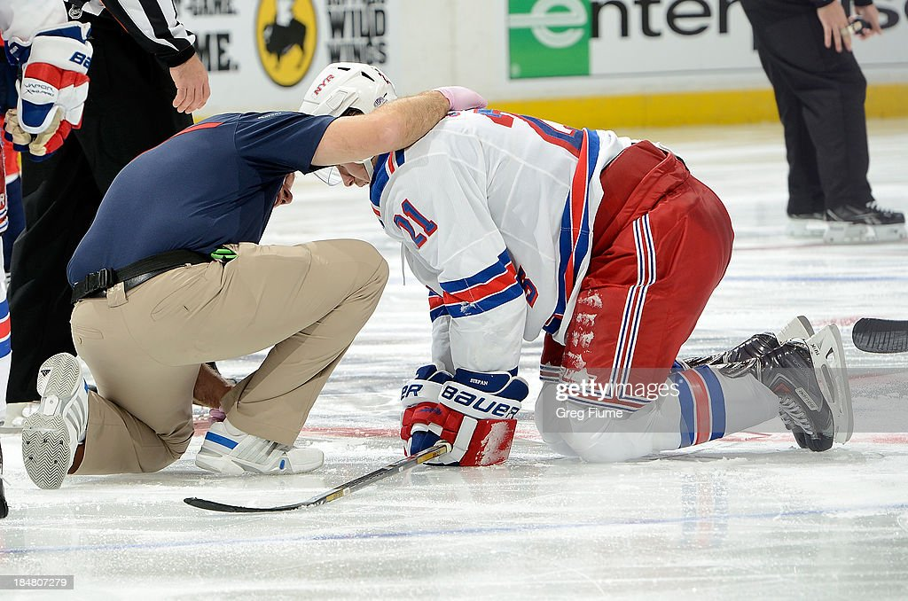 <a gi-track='captionPersonalityLinkClicked' href=/galleries/search?phrase=Derek+Stepan&family=editorial&specificpeople=4687181 ng-click='$event.stopPropagation()'>Derek Stepan</a> #21 of the New York Rangers is helped by by a trainer after being injured in the third period against the Washington Capitals at the Verizon Center on October 16, 2013 in Washington, DC.