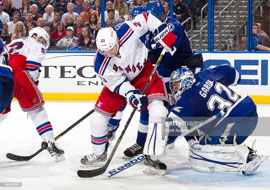 <a gi-track='captionPersonalityLinkClicked' href=/galleries/search?phrase=Derek+Stepan&family=editorial&specificpeople=4687181 ng-click='$event.stopPropagation()'>Derek Stepan</a> #21 of the New York Rangers looses control of the puck while goalie <a gi-track='captionPersonalityLinkClicked' href=/galleries/search?phrase=Mathieu+Garon&family=editorial&specificpeople=206119 ng-click='$event.stopPropagation()'>Mathieu Garon</a> #32 of the Tampa Bay Lightning defends during the second period of their game at the Tampa Bay Times Forum on February 2, 2013 in Tampa, Florida.