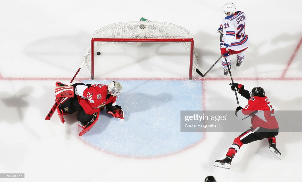 Derek Stepan of the New York Rangers scores a third period goal against Nathan Lawson and Cody Ceci of the Ottawa Senators at Canadian Tire Centre on...