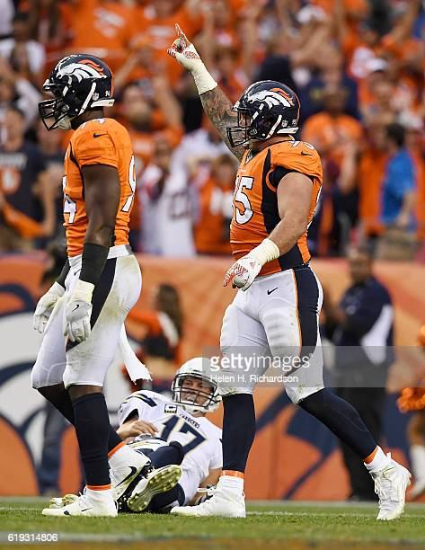 Derek Wolfe of the Denver Broncos and DeMarcus Ware celebrate as Philip Rivers of the San Diego Chargers lies on the grass after getting knocked down...