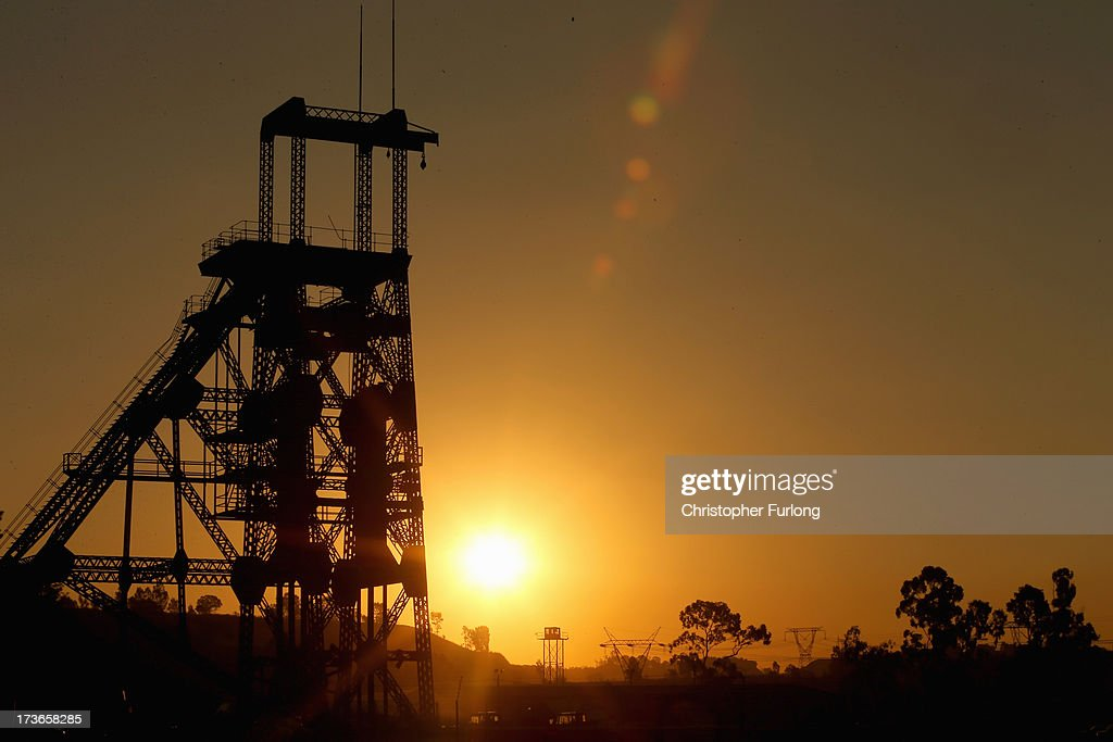 A derelict gold mine shaft's winding gear sits in front of the setting sun on July 15 2013 in Johannesburg South Africa Johannesburg became the...