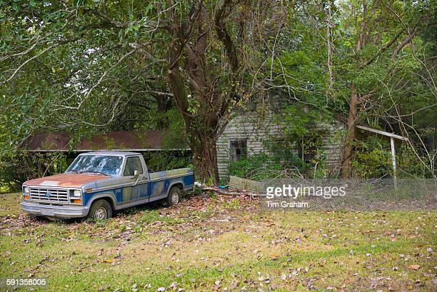 Derelict rundown old Cajun shack and rusty Ford F150 pickup truck in Louisiana USA