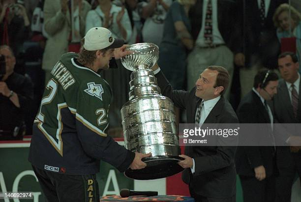 Derian Hatcher of the Dallas Stars takes the Stanley Cup from NHL commissioner Gary Bettman after the Stars defeated the Buffalo Sabres in Game 6 of...