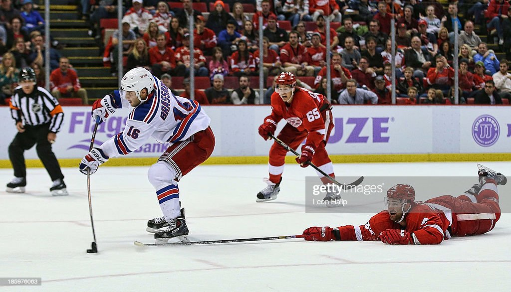 <a gi-track='captionPersonalityLinkClicked' href=/galleries/search?phrase=Derick+Brassard&family=editorial&specificpeople=540468 ng-click='$event.stopPropagation()'>Derick Brassard</a> #16 of the New York Rangers breaks away from <a gi-track='captionPersonalityLinkClicked' href=/galleries/search?phrase=Kyle+Quincey&family=editorial&specificpeople=2234340 ng-click='$event.stopPropagation()'>Kyle Quincey</a> #27 of the Detroit Red Wings and scores the game-winning goal in overtime during the game at Joe Louis Arena on October 26, 2013 in Detroit, Michigan. The Rangers defeated the Red Wings 3-2.