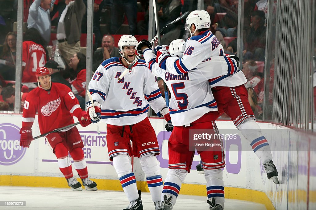 Derick Brassard #16 of the New York Rangers celebrates his over time game winning goal with teammates Benoit Pouliot #67 and Dan Girardi #5 during an NHL game against the Detroit Red Wings at Joe Louis Arena on October 26, 2013 in Detroit, Michigan. The Rangers won in O