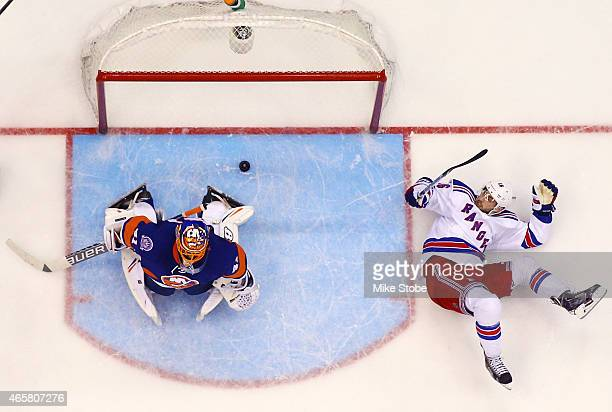 Derick Brassard of the New York Rangers falls to the ice as Jaroslav Halak of the New York Islanders allows a third period goal on a shot by Rick...