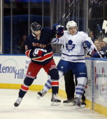 Derick Brassard of the New York Rangers hits Nikolai Kulemin of the Toronto Maple Leafs into the boards during the first period at Madison Square...