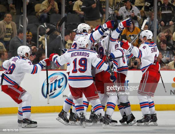 Derick Brassard of the New York Rangers is congratulated by teammates after his overtime goal against the Pittsburgh Penguins in Game One of the...