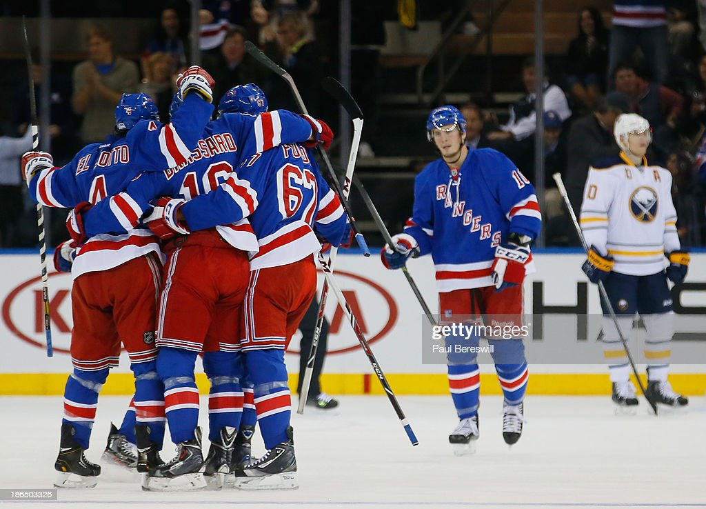 <a gi-track='captionPersonalityLinkClicked' href=/galleries/search?phrase=Derick+Brassard&family=editorial&specificpeople=540468 ng-click='$event.stopPropagation()'>Derick Brassard</a> #16 of the New York Rangers is mobbed by teammates after scoring the first goal in the first period of an NHL hockey game against the Buffalo Sabres at Madison Square Garden on October 31, 2013 in New York City.