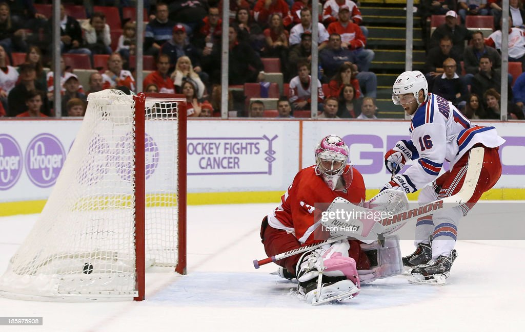 <a gi-track='captionPersonalityLinkClicked' href=/galleries/search?phrase=Derick+Brassard&family=editorial&specificpeople=540468 ng-click='$event.stopPropagation()'>Derick Brassard</a> #16 of the New York Rangers scores the game winner goal in overtime againat golie <a gi-track='captionPersonalityLinkClicked' href=/galleries/search?phrase=Jimmy+Howard&family=editorial&specificpeople=2118637 ng-click='$event.stopPropagation()'>Jimmy Howard</a> #35 of the Detroit Red Wings at Joe Louis Arena on October 26, 2013 in Detroit, Michigan. The Rangers defeated the Red Wings 3-2.
