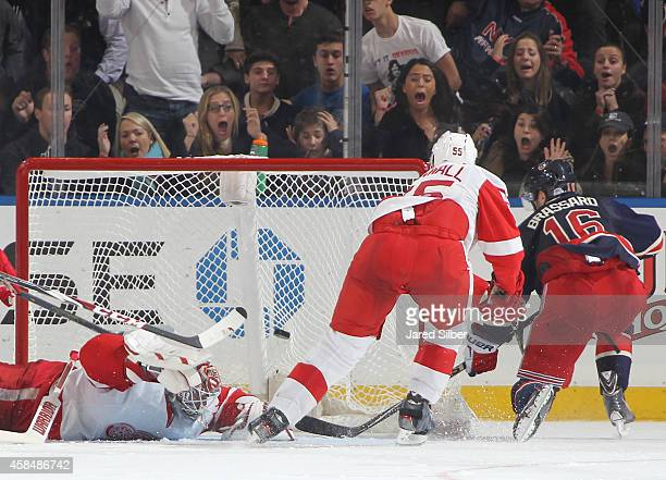 Derick Brassard of the New York Rangers scores the game winning goal in overtime against Jonas Gustavsson of the Detroit Red Wings at Madison Square...