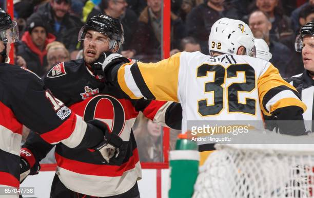 Derick Brassard of the Ottawa Senators and Mark Streit of the Pittsburgh Penguins grab at each other during a scrum at Canadian Tire Centre on March...