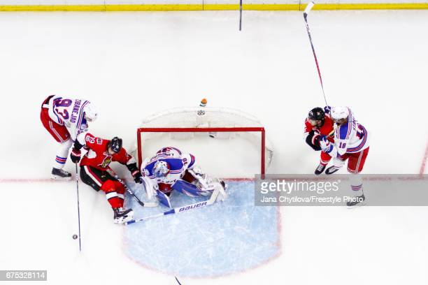 Derick Brassard of the Ottawa Senators controls the puck from a sitting position as Henrik Lundqvist of the New York Rangers loses his stick and Mika...