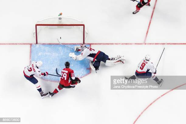 Derick Brassard of the Ottawa Senators gets the puck past a sprawling Braden Holtby of the Washington Capitals as Matt Niskanen and Dmitry Orlov of...