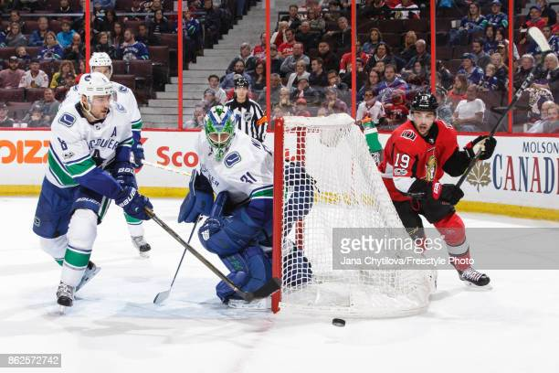 Derick Brassard of the Ottawa Senators skates after the puck as Christopher Tanev and Anders Nilsson of the Vancouver Canucks defend the net in the...