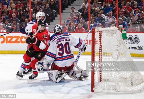 Derick Brassard of the Ottawa Senators skates past Henrik Lundqvist of the New York Rangers as Mika Zibanejad of the New York Rangers looks on in...