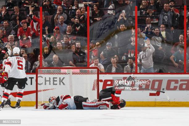 Derick Brassard of the Ottawa Senators tumbles over Cory Schneider of the New Jersey Devils as he scores a second period goal at Canadian Tire Centre...