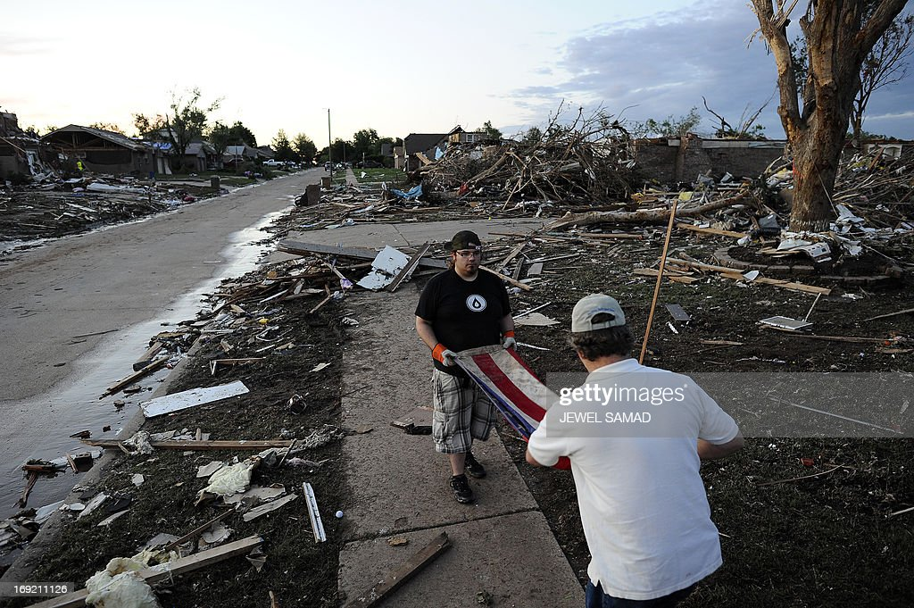 Derick Brock from Mercy Chefs (R) helps a man to fold a US flag he found in the debris of a tornado devastated house on May 21, 2013 in Moore, Oklahoma. Families returned to a blasted moonscape that had been an American suburb Tuesday after a monstrous tornado tore through the outskirts of Oklahoma City, killing at least 24 people. Nine children were among the dead and entire neighborhoods vanished, with often the foundations being the only thing left of what used to be houses and cars tossed like toys and heaped in big piles. AFP PHOTO/Jewel Samad