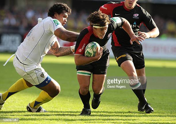 Derick Hougaard of Saracens is tackled by Sione Lauaki during the Heineken Cup match between ASM Clermont Auvergne and Saracens at Stade Marcel...