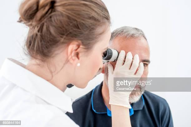 Dermatologue, inspectant les taupes de peau sur le visage de patients