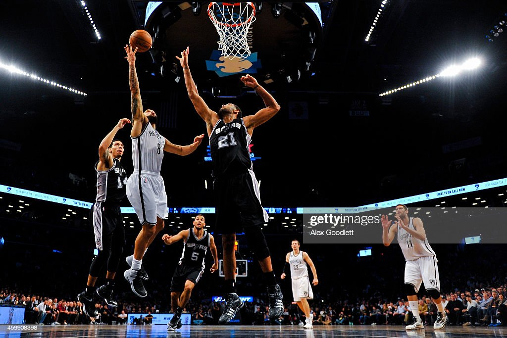 Deron Williams of the Brooklyn Nets attempts a shot over Tim Duncan of the San Antonio Spurs in overtime at the Barclays Center on December 3 2014 in...