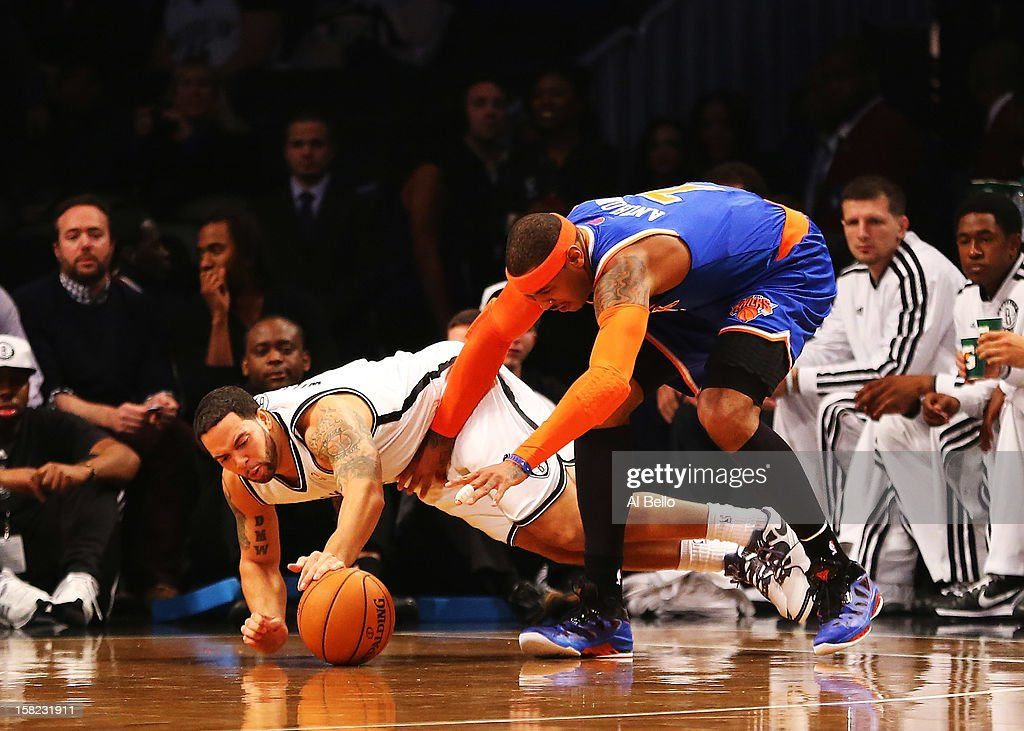 Deron Williams #8 of the Brooklyn Nets dives for the ball as Carmelo Anthony #7 of the New York Knicks defends during their game at the Barclays Center on December 11, 2012 in the Brooklyn borough of New York City.