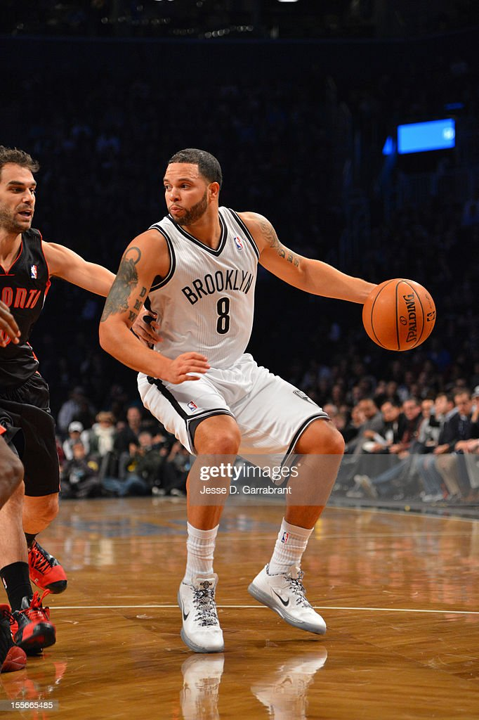 Deron Williams #8 of the Brooklyn Nets drives against Jose Calderon #8 of the Toronto Raptors during the first ever regular home season game at the Barclays Center on November 3, 2012 in the Brooklyn borough of New York City.