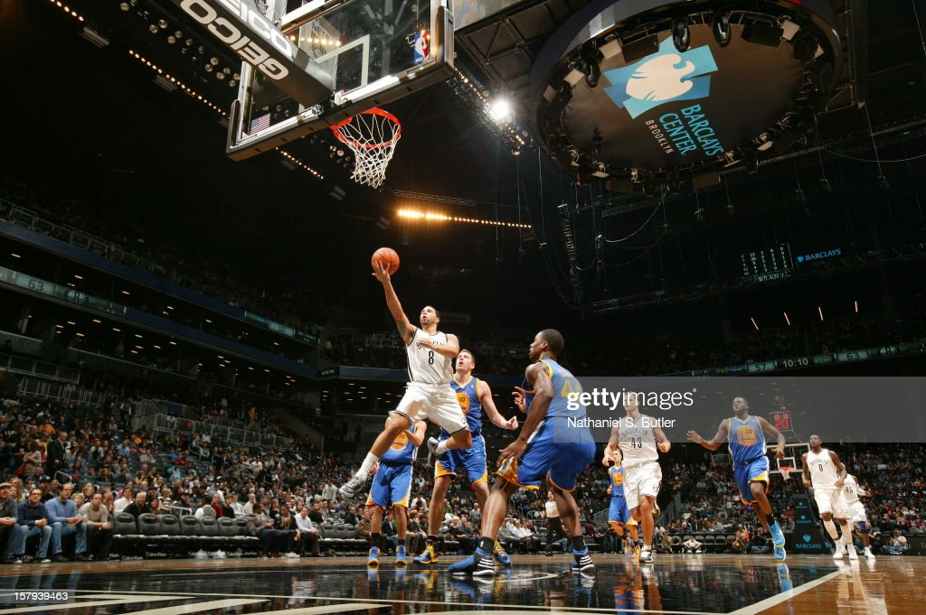 <a gi-track='captionPersonalityLinkClicked' href=/galleries/search?phrase=Deron+Williams&family=editorial&specificpeople=203215 ng-click='$event.stopPropagation()'>Deron Williams</a> #8 of the Brooklyn Nets drives to the basket against David Lee #10 and <a gi-track='captionPersonalityLinkClicked' href=/galleries/search?phrase=Harrison+Barnes&family=editorial&specificpeople=6893973 ng-click='$event.stopPropagation()'>Harrison Barnes</a> #40 of the Golden State Warriors on December 7, 2012 at the Barclays Center in the Brooklyn Borough of New York City.
