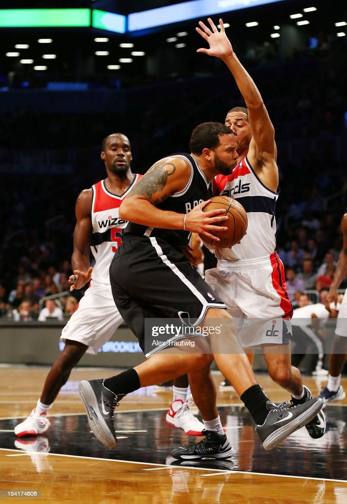 Deron Williams #8 of the Brooklyn Nets drives to the basket as Jannero Pargo #7 and Emeka Okafor #50 of the Washington Wizards defends during a preseason game at the Barclays Center on October 15, 2012 in the Brooklyn borough of New York City.