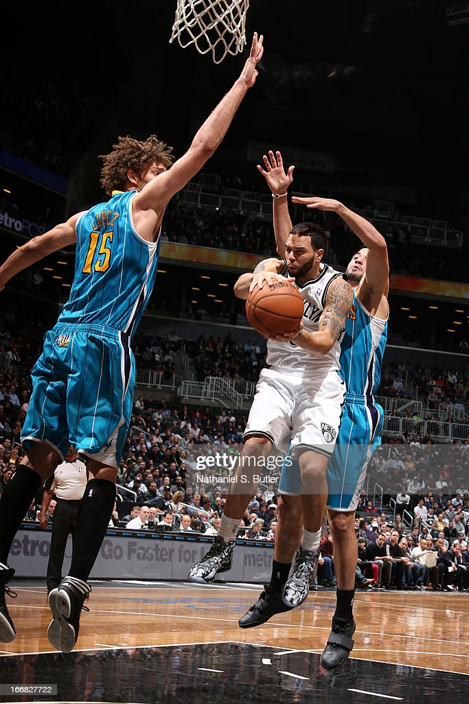 Deron Williams #8 of the Brooklyn Nets goes to the basket against Greivis Vasquez #21 and Robin Lopez #15 of the New Orleans Hornets on March 12, 2013 at the Barclays Center in the Brooklyn borough of New York City.