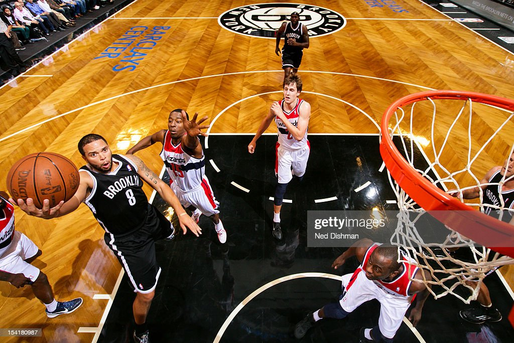 <a gi-track='captionPersonalityLinkClicked' href=/galleries/search?phrase=Deron+Williams&family=editorial&specificpeople=203215 ng-click='$event.stopPropagation()'>Deron Williams</a> #8 of the Brooklyn Nets goes to the basket against <a gi-track='captionPersonalityLinkClicked' href=/galleries/search?phrase=Jordan+Crawford&family=editorial&specificpeople=4779380 ng-click='$event.stopPropagation()'>Jordan Crawford</a> #15 of the Washington Wizards at the Barclays Center on October 15, 2012 in the Brooklyn borough of New York City.