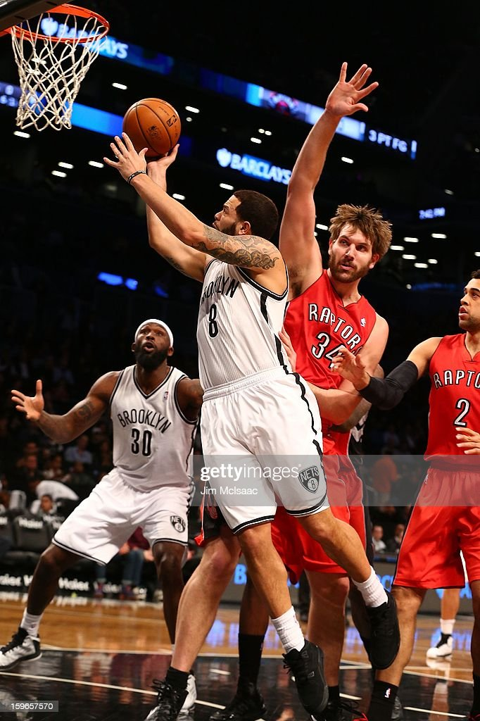 Deron Williams #8 of the Brooklyn Nets in action against Aaron Gray #34 of the Toronto Raptors at Barclays Center on January 15, 2013 in the Brooklyn borough of New York City.The Nets defeated the Raptors 113-106.