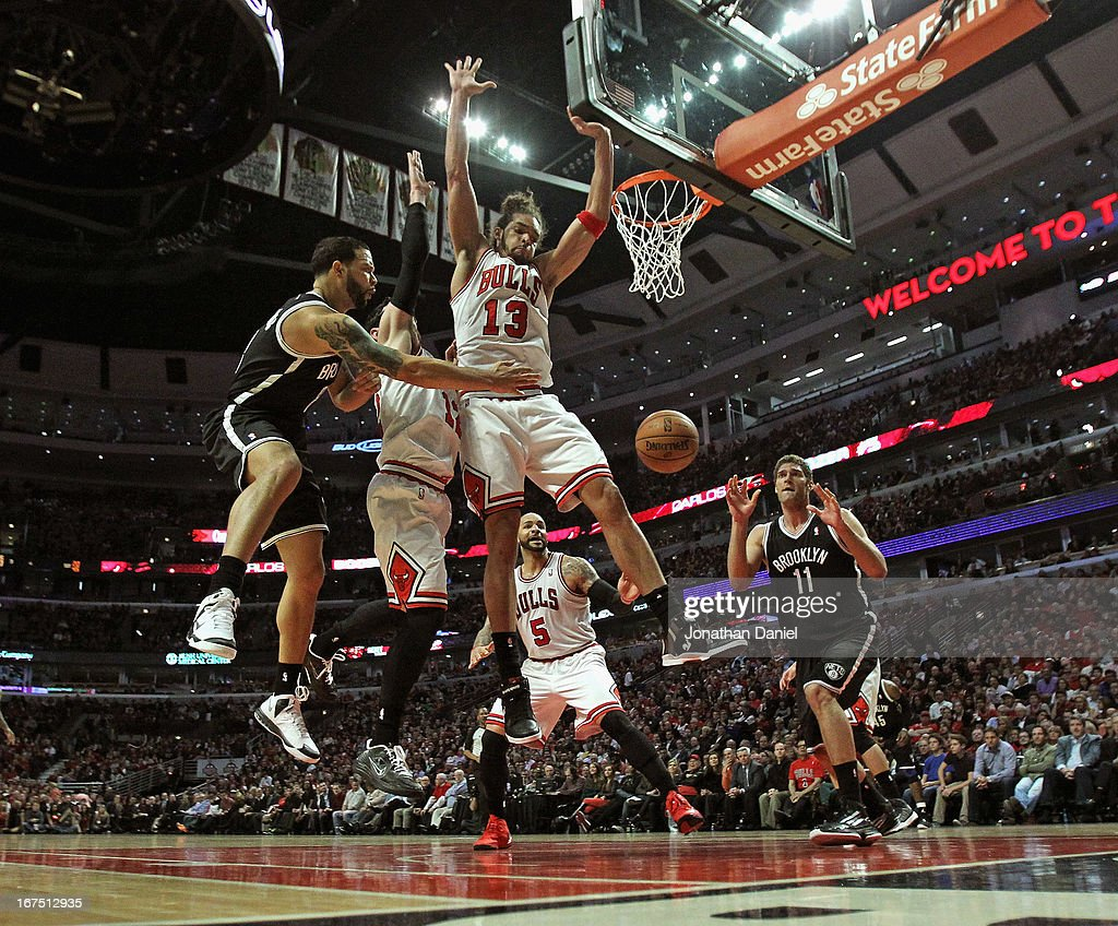 Deron Williams of the Brooklyn Nets passes the ball to Brook Lopez around Joakim Noah and Kirk Hinrich of the Chicago Bulls in Game Three of the...