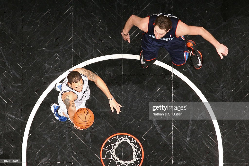 <a gi-track='captionPersonalityLinkClicked' href=/galleries/search?phrase=Deron+Williams&family=editorial&specificpeople=203215 ng-click='$event.stopPropagation()'>Deron Williams</a> #8 of the Brooklyn Nets shoots a layup against <a gi-track='captionPersonalityLinkClicked' href=/galleries/search?phrase=Josh+McRoberts&family=editorial&specificpeople=732530 ng-click='$event.stopPropagation()'>Josh McRoberts</a> #11 of the Charlotte Bobcats on April 6, 2013 at the Barclays Center in the Brooklyn borough of New York City.