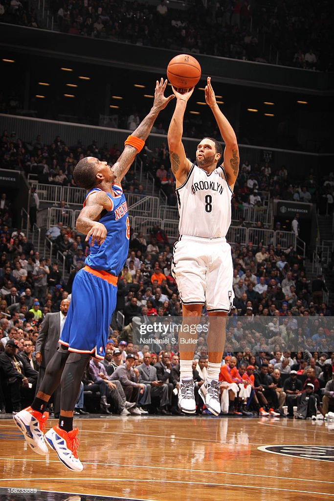 Deron Williams #8 of the Brooklyn Nets shoots against J.R. Smith #8 of the New York Knicks December 11, 2012 at the Barclays Center in the Brooklyn borough of New York City.