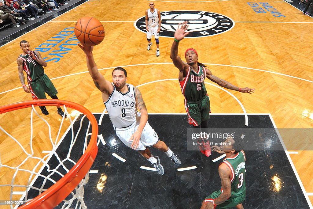 Deron Williams #8 of the Brooklyn Nets shoots the ball against Marquis Daniels #6 and Brandon Jennings #3 of the Milwaukee Bucks during the game at the Barclays Center on December 9, 2012 in Brooklyn, New York.