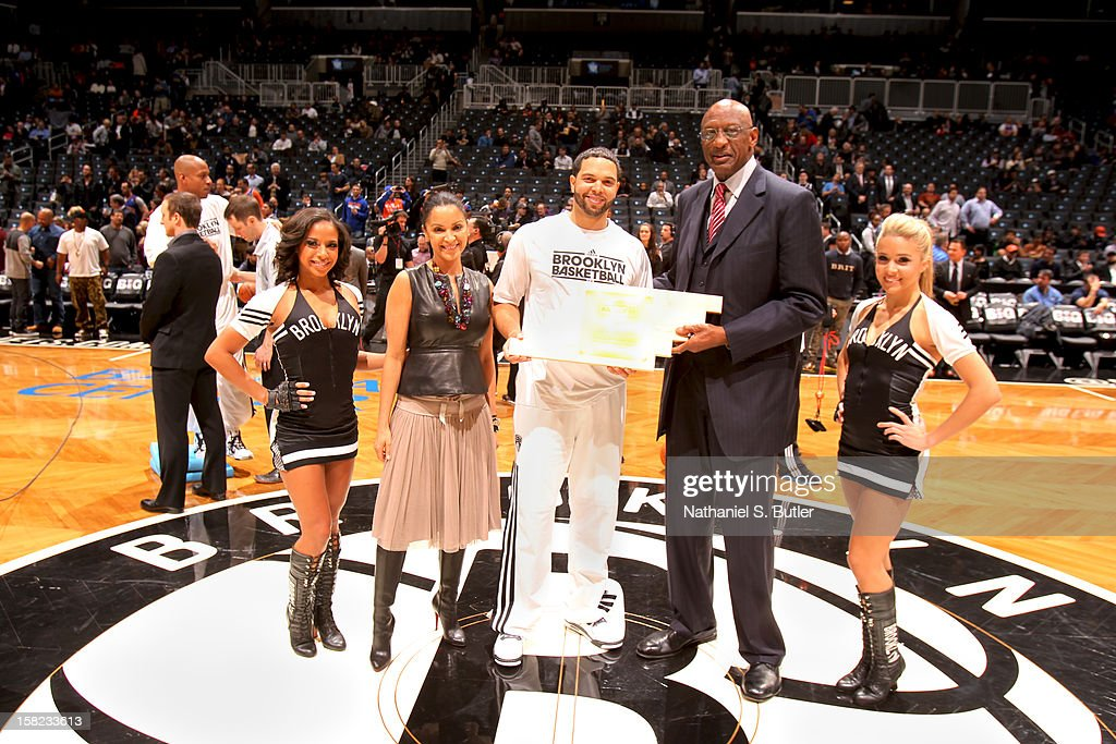 Deron WIlliams #8 of the Brooklyn Nets stands with Petra Pope, Senior VP of Event Marketing and Community Relations, and NBA Cares Ambassador, Bob Lanier to receive an Award on December 11, 2012 at the Barclays Center in the Brooklyn borough of New York City.