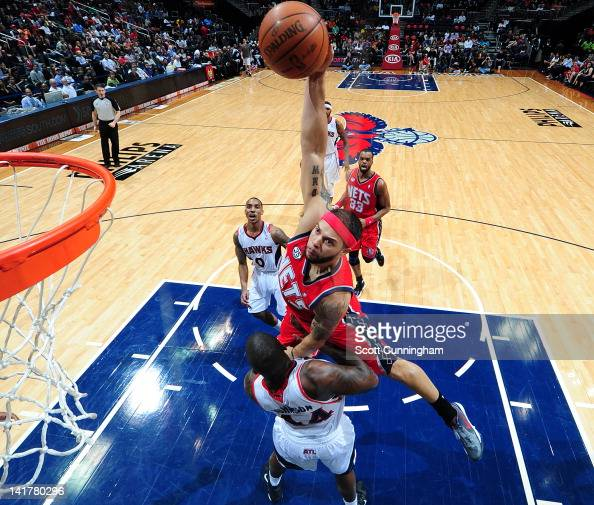 Deron Williams of the New Jersey Nets dunks the ball over Ivan Johnson of the Atlanta Hawks on March 23 2012 at Philips Arena in Atlanta Georgia NOTE...