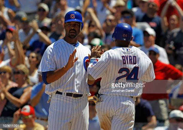 Derrek Lee and Marlon Byrd of the Chicago Cubs celebrate as they score runs in the 6th inning against the Cincinnati Reds at Wrigley Field on July 3...