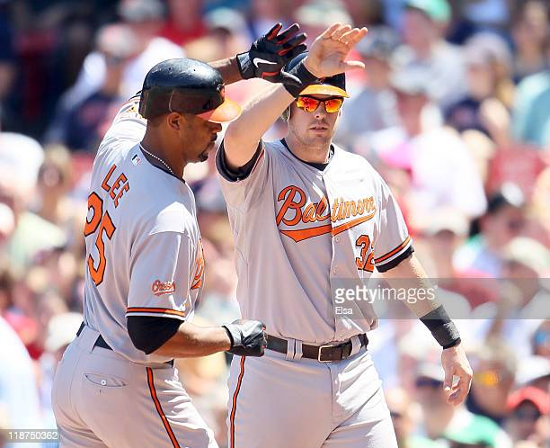 Derrek Lee of the Baltimore Orioles is congratulated by teammate Matt Wieters after Lee hit a two rum homer in the fiirst inning against the Boston...