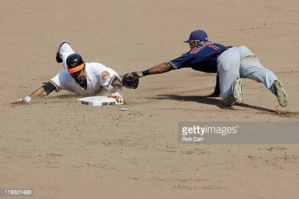Derrek Lee of the Baltimore Orioles slides safely into second base for a double as second baseman Luis Valbuena of the Cleveland Indians applies the...