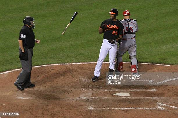 Derrek Lee of the Baltimore Orioles tosses his bat after striking out to end the inning as catcher Ramon Hernandez of the Cincinnati Reds walks away...