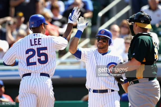 Derrek Lee of the Chicago Cubs highfives teammate Aramis Ramirez after Lee hit a solo home run against the Oakland Athletics during the first inning...